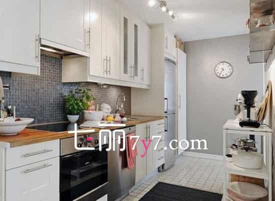这个厨房空间使用白色一字型橱柜,简洁方便,让空间看上去更宽敞明亮,北欧风的舒适休闲理念完全体现而出。橱柜和地砖色彩成对比,视觉感更强。简易的小吧台设计在角落里,很适合浪漫两人行。  不规则的厨房空间也可以装修的很美哦。白色一字型橱柜延伸至不规则的角落,在此摆放上一个精致的收纳柜,实用性很强。